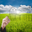 Hand pushing house plan on the blue sky field — Stock Photo
