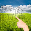 Hand pushing house plan on the blue sky field - Stock Photo