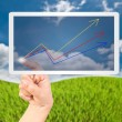 Hans pressing up graph on the tablet in blue sky field. — Stock Photo