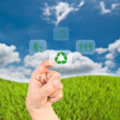 Stock Photo: Hand pressing recycle icon on the grass field.