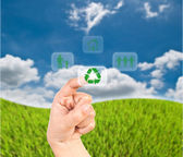 Hand pressing recycle icon on the grass field. — Stock Photo
