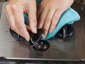 Cleaning dial knob on gas stove top range — Stock Photo
