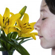 Stock Photo: Girl enjoying smell of flower in full bloom