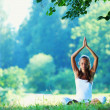 Young woman doing yoga exercise in green park — Stock Photo #10739024