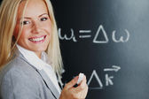 Young woman teacher in front of a blackboard — Stock Photo