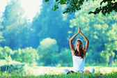 Young woman doing yoga exercise in green park — Stock Photo