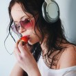 Woman in phones eating strawberry - Stock Photo