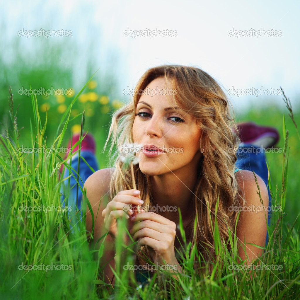 Girl blow on dandelion on green field — Stock Photo #10832850