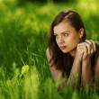 Brunette lying on green grass — Stock Photo