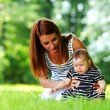 Mother and daughter on the green grass — Stock Photo #11017042