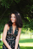 Flicka på en bakgrund av gröna träd — Stockfoto