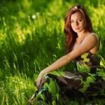 Brunette sitting on green grass — Stock Photo #11271559