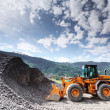 Excavator in alps - Stock Photo