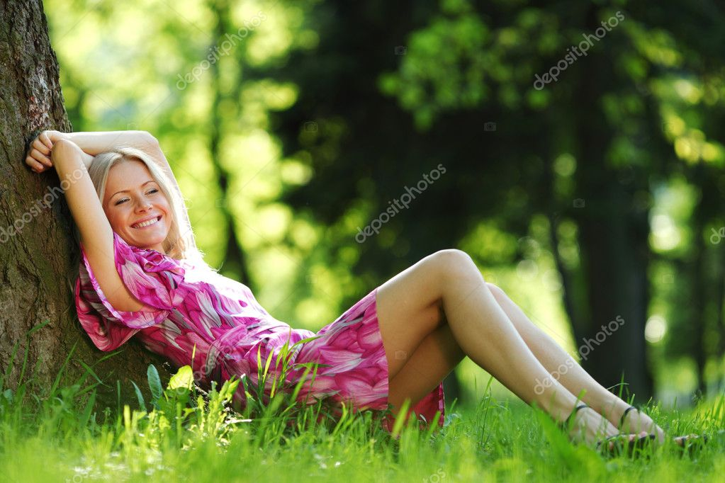 Happy girl lying under a tree on a summer day  Stock Photo #11287821