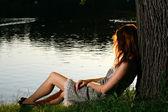 Dziewczyna siedzi na brzegu tha rzeki — Zdjęcie stockowe