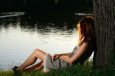 Mädchen sitzen am tha ufer des flusses — Stockfoto