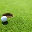 Stock Photo: Golf ball on lip of cup
