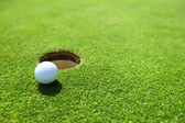 Golf ball op lip van cup — Stockfoto