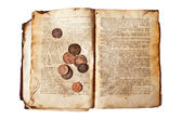 Old decrepit book with copper coins — Stock Photo