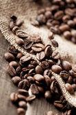 Kaffebönor och säckväv tyg — Stockfoto