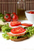 Tasty sandwich with bacon, tomato and salad — Stock Photo