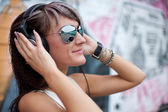 Girl in sunglasses and headphones — Stock Photo