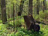 Old rusty garden tool wheelbarrow metal fence — Stock Photo