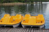 Yellow water bicycles locked at lake pier — Stock Photo