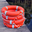 Life savers buoys orange stack wooden lake pier — Stock Photo