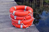 Salva-vidas bóias cais de madeira lago de pilha laranja — Fotografia Stock