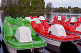 Water bicycles green and red locked at lake pier — Stock Photo