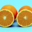 Orange fruit full and sectioned on blue background — Stock Photo
