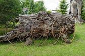 Starý rezavý kočáru opřít do starý kmen stromu — Stock fotografie