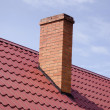 Brown tiled roof yellow brick chimney on sky — Stock Photo