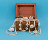 Pearl jewelry in retro wooden box on blue — Stock Photo