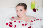 Young beautiful woman relaxing in a bath — Stock Photo