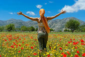 Happy young woman standing in flower colorful field on Lasithi P — Stock Photo