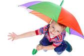Little boy sitting under umbrella — Stock Photo