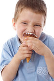 Squinting boy eating ice cream — Stock Photo