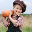 Smiling boy with pumpkin on his shoulder - Stok fotoğraf