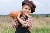 Smiling boy with pumpkin on his shoulder — Φωτογραφία Αρχείου