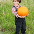 Smiling boy standing with pumpkin — Stock Photo #11508009