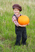 Smiling boy standing with pumpkin — Stock Photo