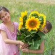 Two kids with sunflowers  in a wheat field — Stock Photo