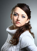 Beautiful girl in sweater. Isolated on a gray background. — Stock Photo