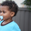 Young multiracial boy with a pacifier — Stock Photo #11388332