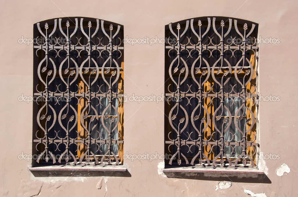 Two old windows with ornamental metal gratings — Stock Photo #11400136