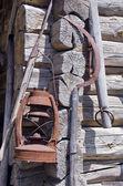 Rusty sickle and kerosene lamp on old farm wall — Stock Photo