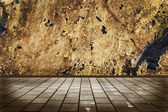 Interior room with stone floor tiles and a stone wall grunge — Stock Photo