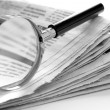 Newspaper and a magnifying glass — Stock Photo